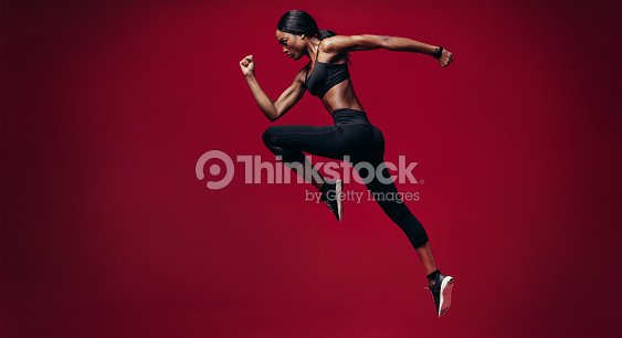 Sports woman running over red background : Foto stock