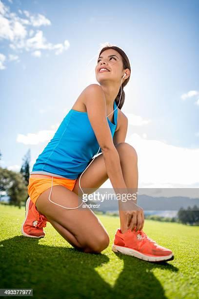 スポーツの女性彼女の靴の結束