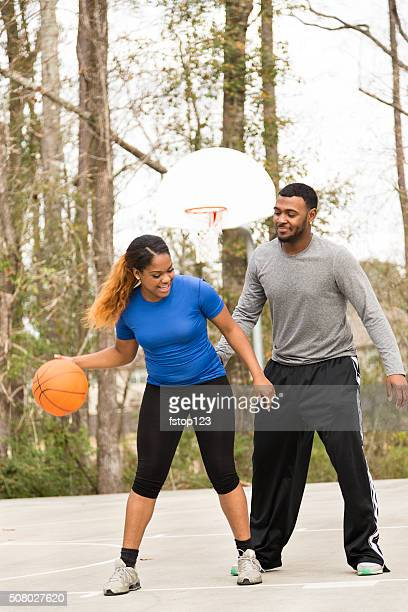 Sports: Young African descent couple play basketball at urban park.