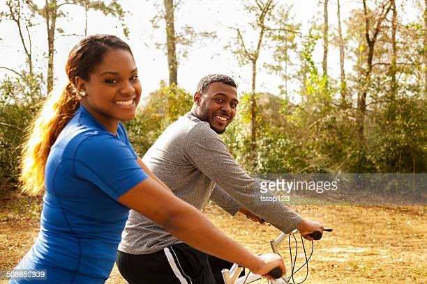 Sports: Young African descent couple ride bikes in neighborhood.