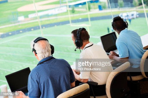 Sportscasters watching and calling a football game in press box