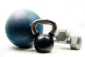 Black and silver kettlebell, blue medicine ball, and silver dumbbells