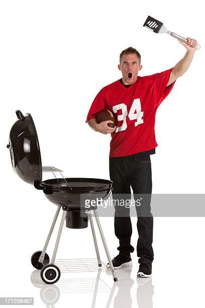 Desportista barbecuing alimentos e Gritar