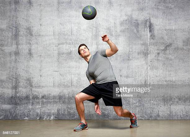 Sportsman catching ball in urban studio setting
