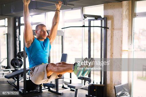 Sportsman doing abs workout on horizontal bar