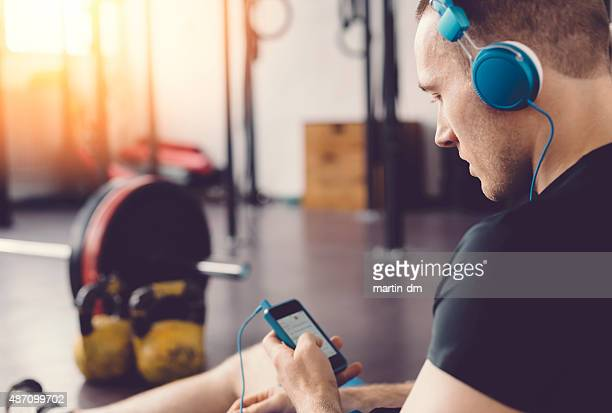 Sportsman in the gym texting on smartphone