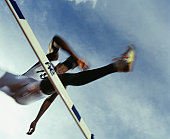Sportsman jumping over hurdles, view from below