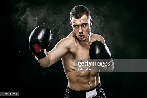 Sportsman muay thai boxer fighting in gloves in boxing cage. Isolated on black background with smoke. Copy Space. : Stock Photo