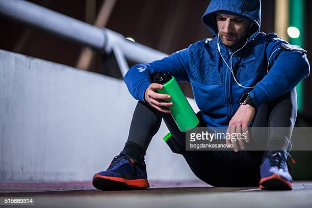 Sportsman sitting on the ground and drinking water