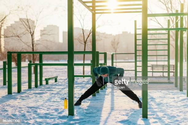 Sportsman stretching after training on cold winter day