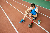 Full length portrait of young amputee athlete sitting on running track taking break from practice to relax and checki fitness bracelet, copy space