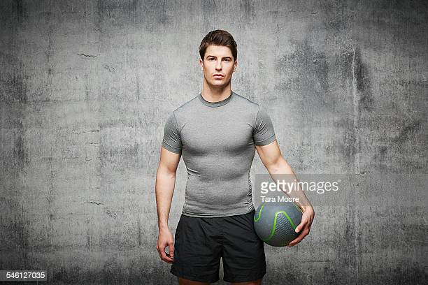 Sportsman with weight ball in urban stud