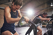 Young sportsmen having hard workout and grimacing on cycling machines in light gym.