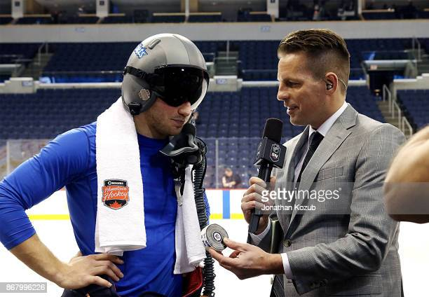 Sportsnet reporter Sean Reynolds presents Brendan Lemieux of the Winnipeg Jets with his official first goal puck during a postgame interview...