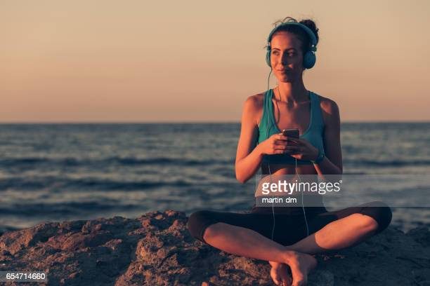 Sportswoman at the beach listening to the music