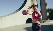 Sportswoman doing boxing working outdoors. Female practicing boxing, throwing a punch in front.