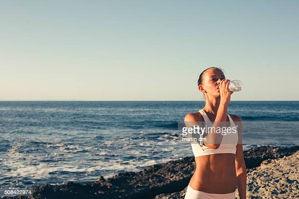 Sportswoman drinking water at the beach