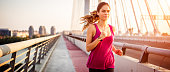 Female athlete running over the bridge early in the morning during her cardio routine. She has smart watch on her wrist.