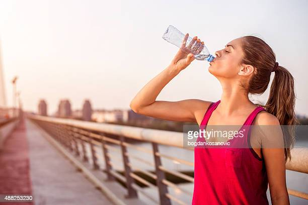 Sportswoman hydrating on the bridge