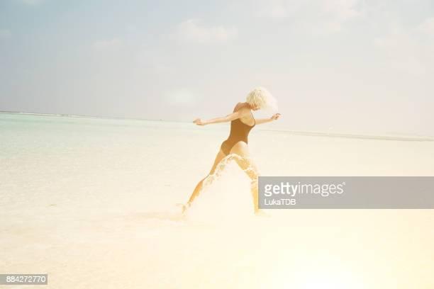 Sportswoman in swimsuit running through shallow water, Maldives