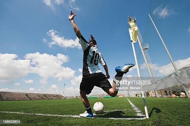 Sportswoman kicking soccer ball