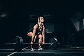 Young athletic sportswoman squatting while lifting a barbell with weights in gym
