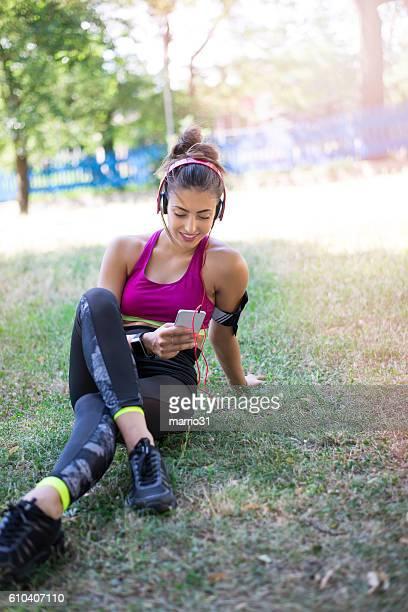 Sportswoman listening to music using smartphone
