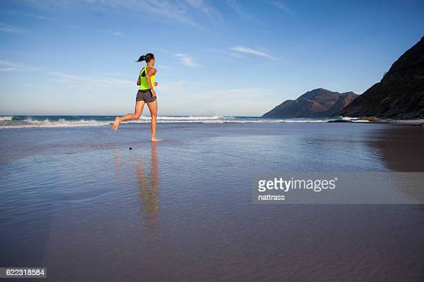 Sportswoman running early morning on the beach