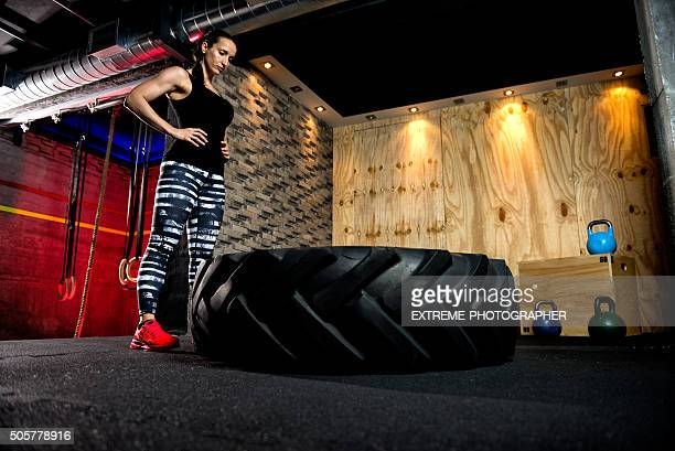 Sportswoman standing next to huge tire