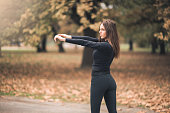 A beautiful young sportswoman is seen stretching her arms in the woods.