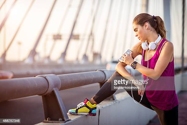Sportswoman stretching leg on the bridge after cardio session