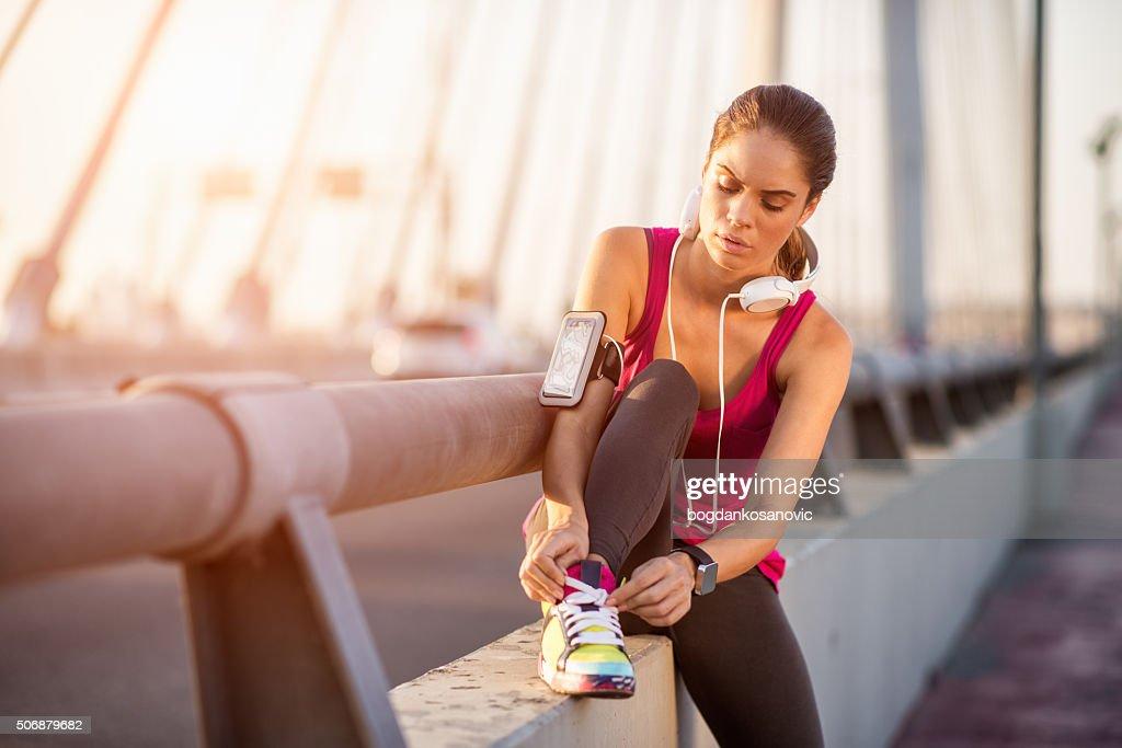 Sportswoman tying shoe lace
