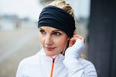 Close-up portrait of beautiful sportswoman wearing headband and listening to music on earphones. Fitness female looking relaxed outdoors