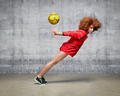 Sportswoman with football suspended in motion