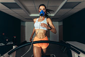 Sportswoman with mask running on treadmill. Female athlete in sports science lab measuring her performance and oxygen consumption.
