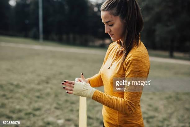 Sportvrouw inwikkeling van handen van boksen wraps