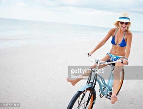Sporty bikini female riding bicycle on beach