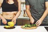 healthy lifestyle, dieting, proper nutrition, vegetarian food, paleo diet. sporty couple cooking dinner together in their kitchen at home. fit people chopping vegetables for salad, close up