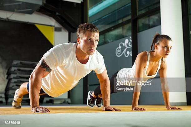 Sporty couple exercising at the fitness gym