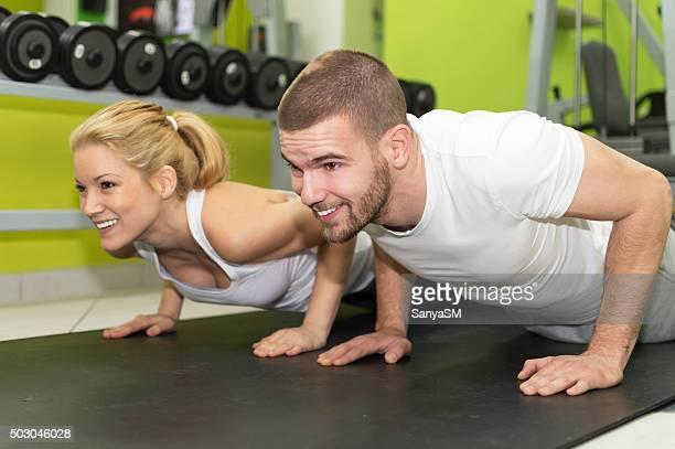 Coppia sportiva esercitando presso la palestra fitness