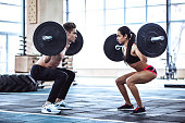Handsome muscular man and attractive sporty woman are working out in gym. Couple making gym training. Squatting with barbells together