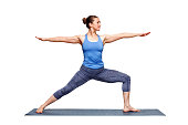 Beautiful sporty fit woman practices  Ashtanga Vinyasa Yoga asana Virabhadrasana 2 - warrior pose 2 isolated on white
