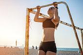 Sporty fit young woman doing pull ups on metal goal frame on sandy beach during sunset.