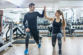 Sporty fitness couple clapping hands together in the gym.
