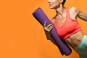 Sporty girl holding yoga mat doing asana