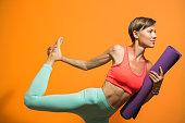 Sporty girl holding yoga mat doing asana
