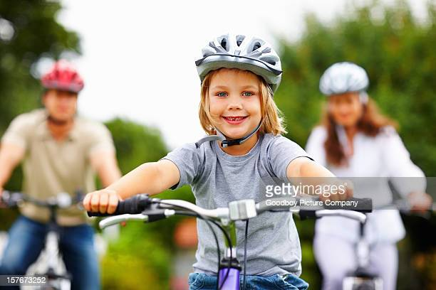 Sporty little boy with his parent in background riding bicycles