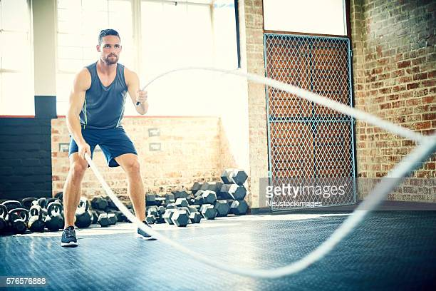Sporty male doing battling rope exercise in gym