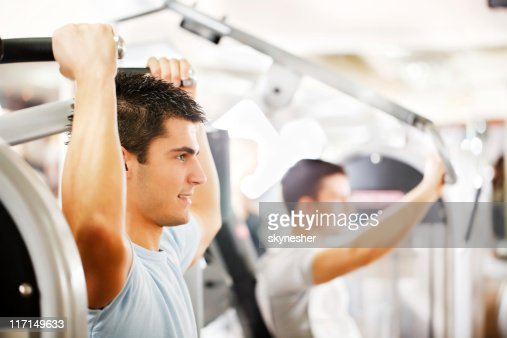 Sporty man is exercising at a modern gym. : Stock Photo