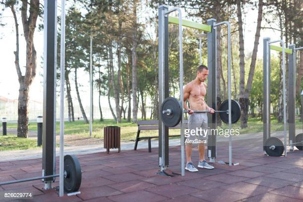 Sporty man lifting weights outdoor in the park